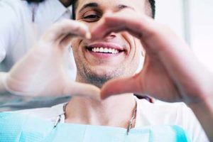 A man and his dentist make a heart with their hands after they talk about Lovett Dental Kohrville