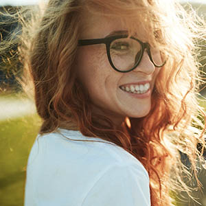 A woman in glasses looks behind her and smiles after receiving dental services at Lovett Dental Kohrville