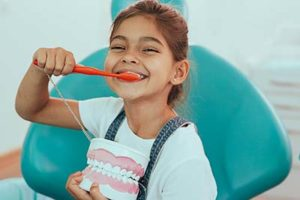 A little girl smiles as she brushes her teeth, showing what she learned using pediatric dentistry in Kohrville, TX